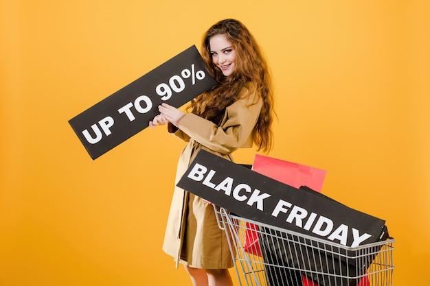 Mulher surpreendida no casaco com sexta-feira preta sinal de 90% e sacolas coloridas no carrinho isolado sobre amarelo