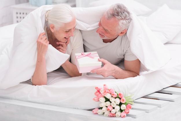 Mulher surpreendida olhando para caixa de presente, dada pelo marido na cama
