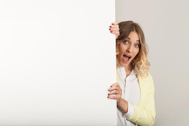 Mulher surpreendida que olha além da porta