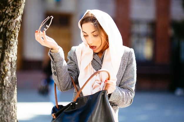 Mulher surpreendida que olha sua bolsa