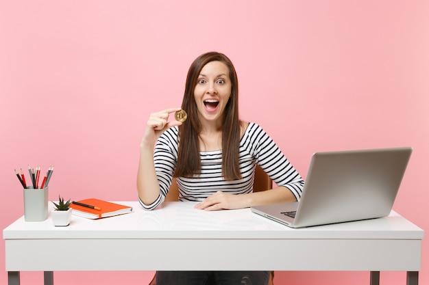 Mulher surpreendida segurando bitcoin, moeda de metal de cor dourada, futura moeda sentada no trabalho na mesa branca com o laptop do pc