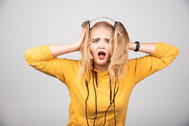 Mulher surpreendida usando fones de ouvido e posando.
