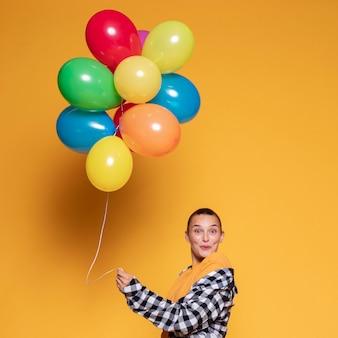 Mulher surpresa com balões coloridos