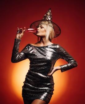Mulher surpresa com rosto lindo e penteado retrô e lábios vermelhos segurando abóbora no estúdio em fundo laranja. projeto de arte ampla festa de halloween. glamour fashion sexy vampire lady com fantasia de bruxa.