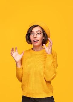 Mulher surpresa com roupas amarelas olhando para a câmera