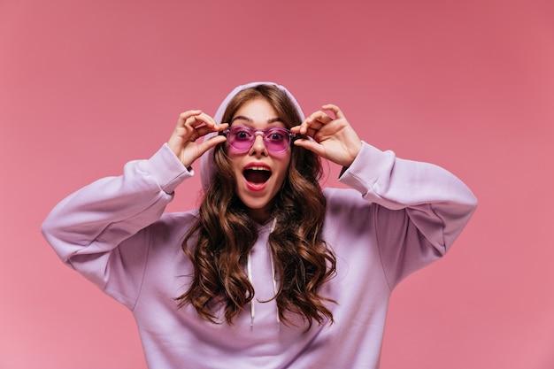 Mulher surpresa com um capuz roxo tirando óculos de sol brilhantes