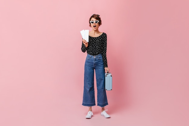Mulher surpresa de jeans segurando ingressos na parede rosa