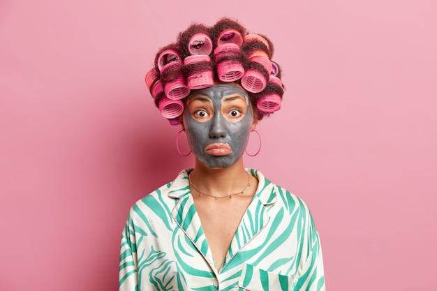Mulher surpresa e chateada franze os lábios aplica máscara de argila para rejuvenescimento da pele faz o penteado perfeito usar roupão de seda isolado sobre a parede rosa. conceito de procedimentos de cuidados com o rosto e beleza
