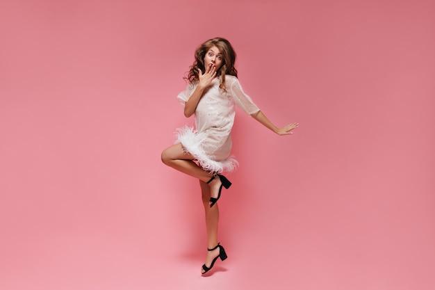 Mulher surpresa em vestido branco pula na parede rosa