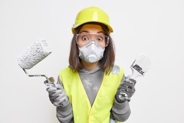 Mulher surpresa, gerente de construção, segura ferramentas de construção, garante a qualidade de sua casa consertando roupas de trabalho