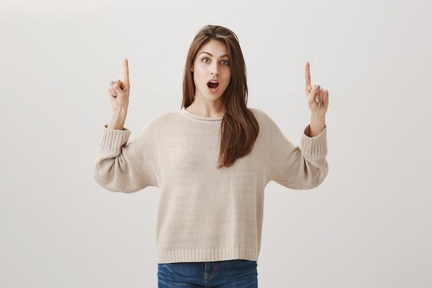 Mulher surpresa mostrando promo, apontando o dedo para cima e o queixo caído em choque