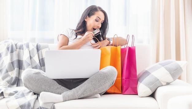 Mulher surpresa olhando para sacos de papel laranja e rosa ao lado dela em um sofá branco, com um cartão de crédito na mão e um computador no colo.