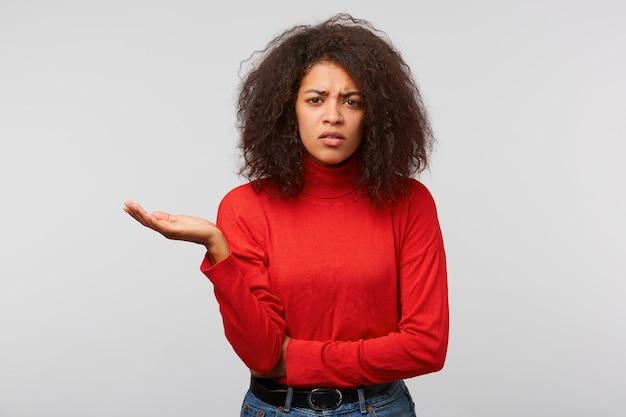 Mulher suspeita com cabelo afro encaracolado em pé, mão dobrada e uma palma levantada