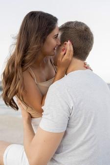 Mulher sussurrando no ouvido do namorado enquanto é segurada por ele