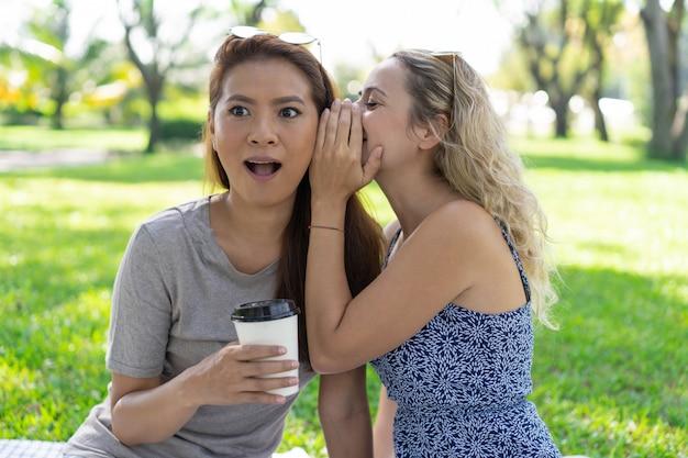 Mulher, sussurrando, segredo, para, surpreendido, amigo feminino, parque