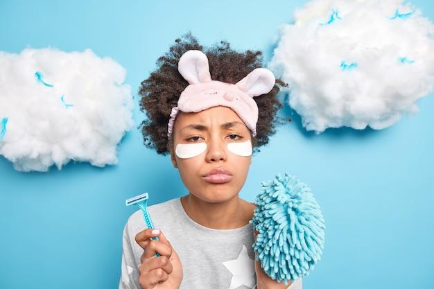 Mulher taciturna infeliz com cabelo encaracolado com expressão sonolenta e insatisfeita segura navalha e esponja de banho cuida de sua pele corpo vestido com pijama isolado sobre parede azul