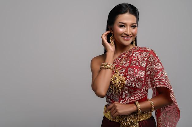 Mulher tailandesa bonita que veste um vestido tailandês e um sorriso feliz.