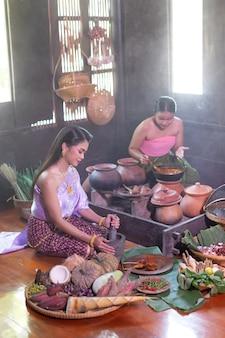 Mulher tailandesa cozinhando em vestido tailandês retrô