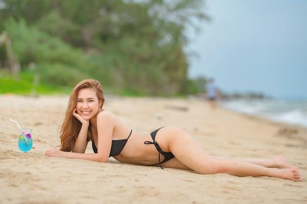 Mulher tailandesa de biquíni preto posando na praia