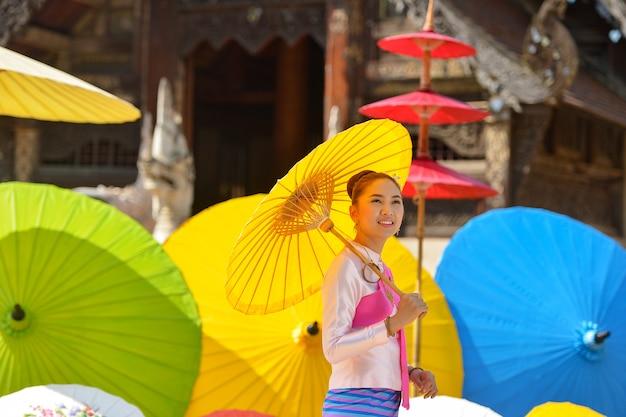 Mulher tailandesa em traje tradicional da tailândia pintando guarda-chuva, chiangmai tailândia, cultura tailandesa, estilo da cultura lanna