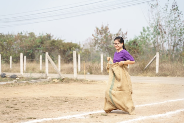Mulher tailandesa fazendo corrida de sacos ou jogo de corrida