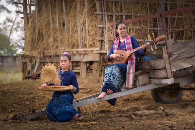 Mulher tailandesa no campo de arroz e atividade de estilo de vida do agricultor conceito de casa de campo Foto Premium