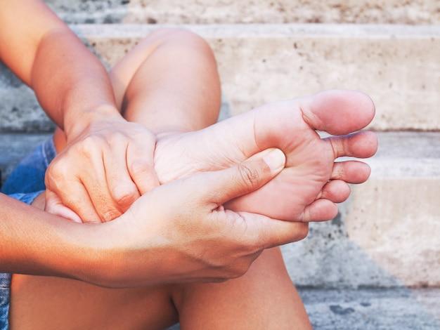 Mulher tailandesa nova que sofre o salto da dor do pé e a sola do pé, use a mão para fazer massagens para relaxar, sintoma médico e conceito dos cuidados médicos.