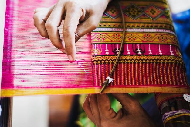 Mulher tailandesa que faz a linha de seda. uma forma tradicional de produção artesanal de seda.