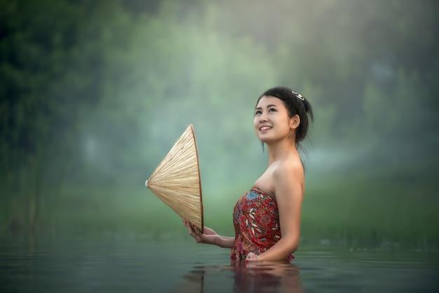 Mulher tailandesa tomando banho no rio