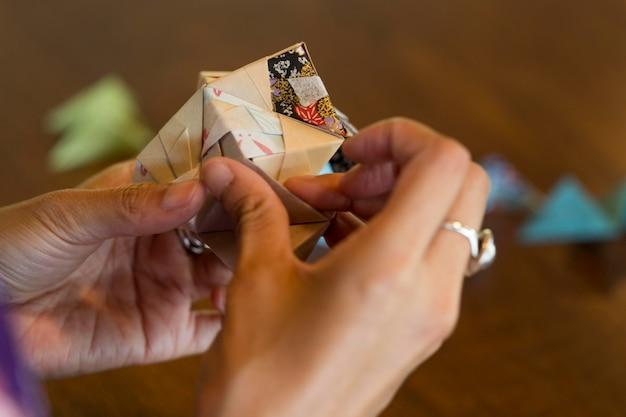 Mulher talentosa fazendo origami com papel japonês