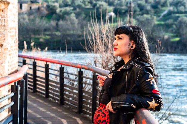 Mulher tatuada alternativa em jaqueta de couro e óculos escuros, encostada em uma grade contemplando a paisagem.