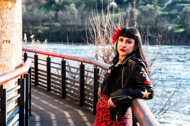 Mulher tatuada alternativa na jaqueta de couro e óculos escuros, encostado em uma grade sobre o rio.