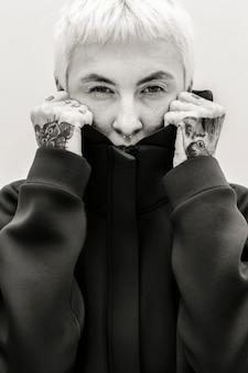 Mulher tatuada cobrindo o rosto com um moletom preto