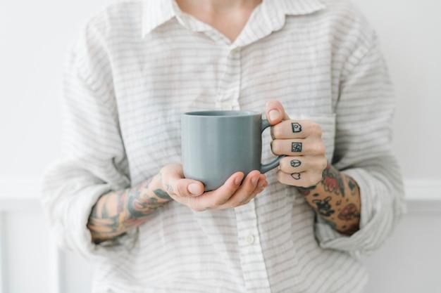 Mulher tatuada com uma xícara de café