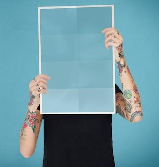 Mulher tatuada segurando um papel em branco