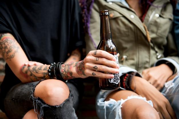 Mulher tatuada segurando uma garrafa de cerveja