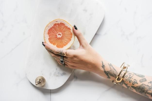 Mulher tatuada segurando uma laranja sobre um fundo de mármore