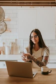 Mulher tatuada trabalhando em casa na cozinha dela
