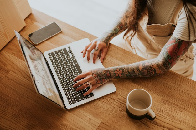 Mulher tatuada trabalhando em seu pequeno negócio em casa