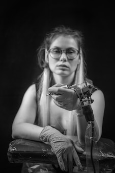 Mulher tatuadora com máquina de tatuagem em estúdio