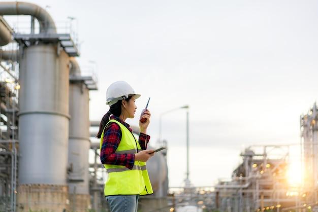 Mulher, técnica, engenheira industrial, usando walkie-talkie e segurando o bluprint