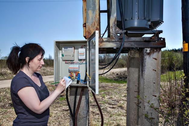 Mulher técnica verificando o medidor de eletricidade e a fatura em pé perto da subestação do transformador de energia do painel de distribuição de eletricidade ao ar livre.
