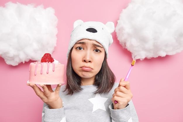 Mulher tem a tentação de comer bolo doce saboroso, mas tem medo de ter problemas com os dentes segura a escova de dentes