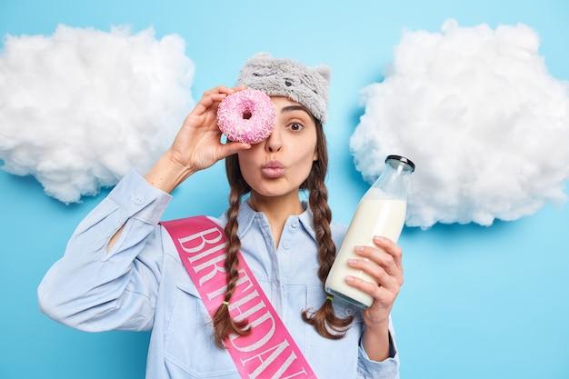 Mulher tem dente doce contra olho com rosquinha saborosa no olho mantém os lábios arredondados desfruta de uma sobremesa deliciosa com leite fresco usa fita de camisa e sleepmasj faz aniversário hoje