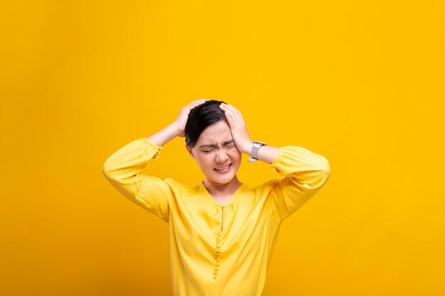 Mulher tem dor de cabeça isolada sobre parede amarela
