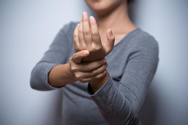 Mulher tem dor nas mãos