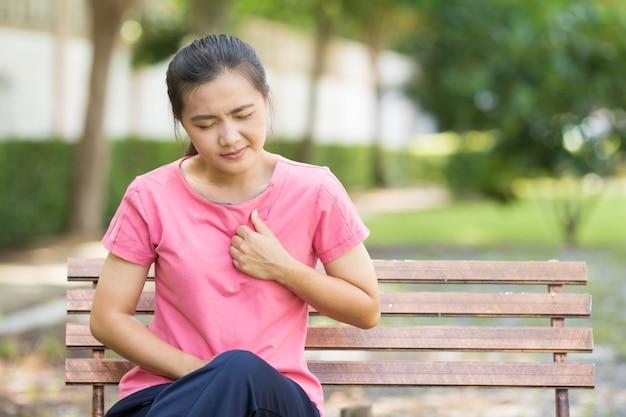 Mulher tem dor no peito no jardim