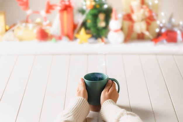 Mulher tem em suas mãos a xícara de café verde sobre fundo desfocado de natal. fotografia em tons quentes. tema café