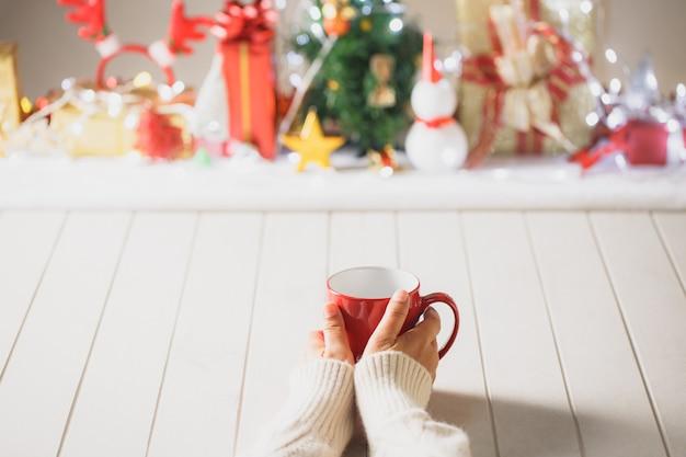 Mulher tem em suas mãos a xícara de café vermelha sobre fundo desfocado de natal. fotografia em tons quentes. tema café
