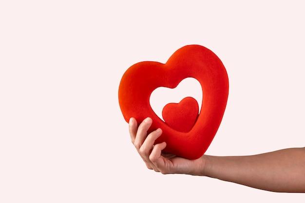 Mulher tem nas mãos um coração vermelho, conceito de dia dos namorados